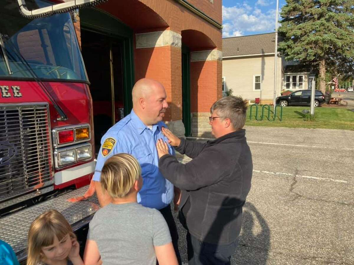 Matt Witkowski (center) participates in a pinning ceremony with his family at the Manistee Fire Department.