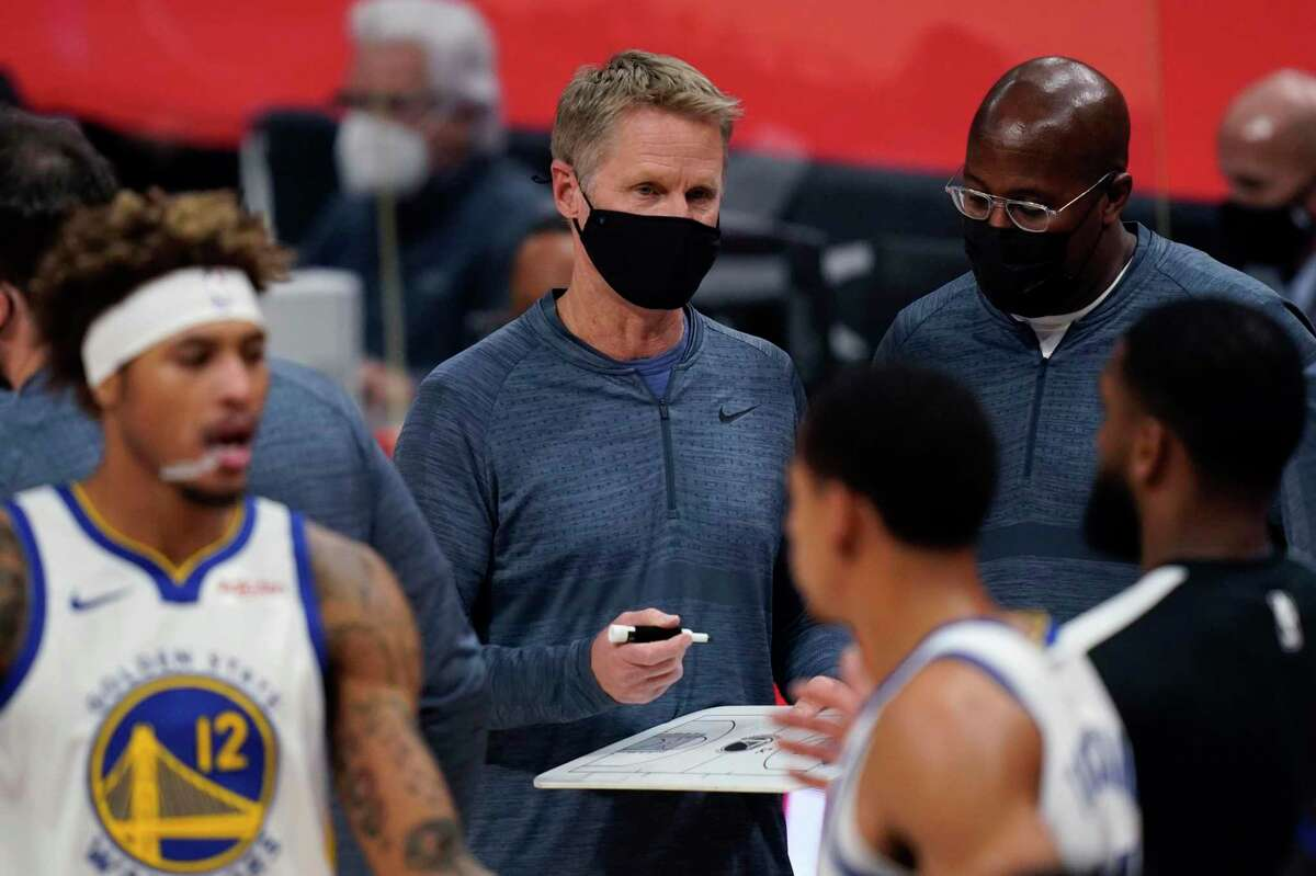 Golden State Warriors coach Steve Kerr holds a court diagram during the second half of the team's NBA basketball game against the Detroit Pistons, Tuesday, Dec. 29, 2020, in Detroit. (AP Photo/Carlos Osorio)