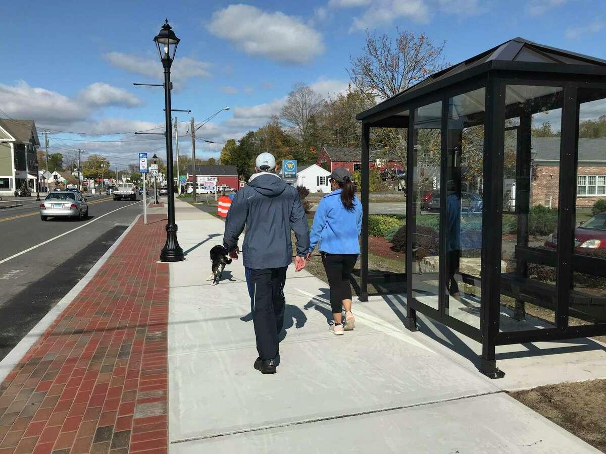 Community members walk their dog along Brookfield's new sidewalks on Oct. 18, 2019.