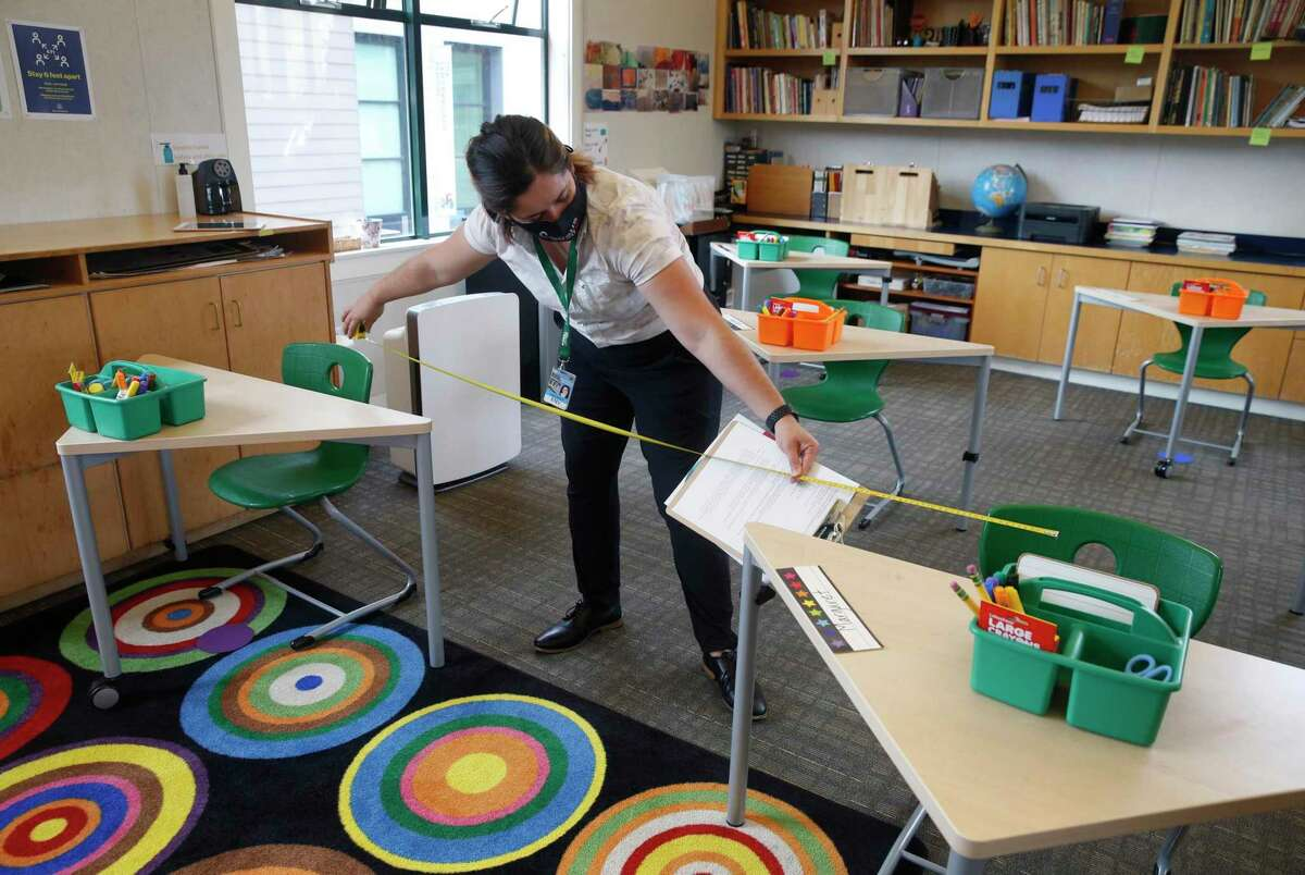 Gianna Fazioli, a safety inspector with the city, measures the distance between desks in a classroom during a tour of the San Francisco School before authorizing in-person learning on the campus in San Francisco on Sept. 17. The private school with 285 students enrolled was among the first schools in the city to apply for in-classroom instruction last year during the coronavirus pandemic.