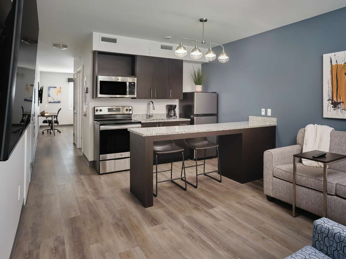 The 500-square-foot rooms at stayAPT Suites offer a distinct living room with a sleeper sofa, a lounge chair, and a 55-inch television; a kitchen with a full-size stove, oven, dishwasher, microwave and refrigerator; and a separate bedroom with a walk-in closet, separate TV and workspace.