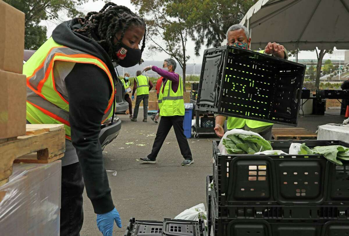 Khimonee Byrd (left), Tina Lee and William Powell of the Alameda County Community Food Bank distribute items at the distribution center on Oakport Street in Oakland.