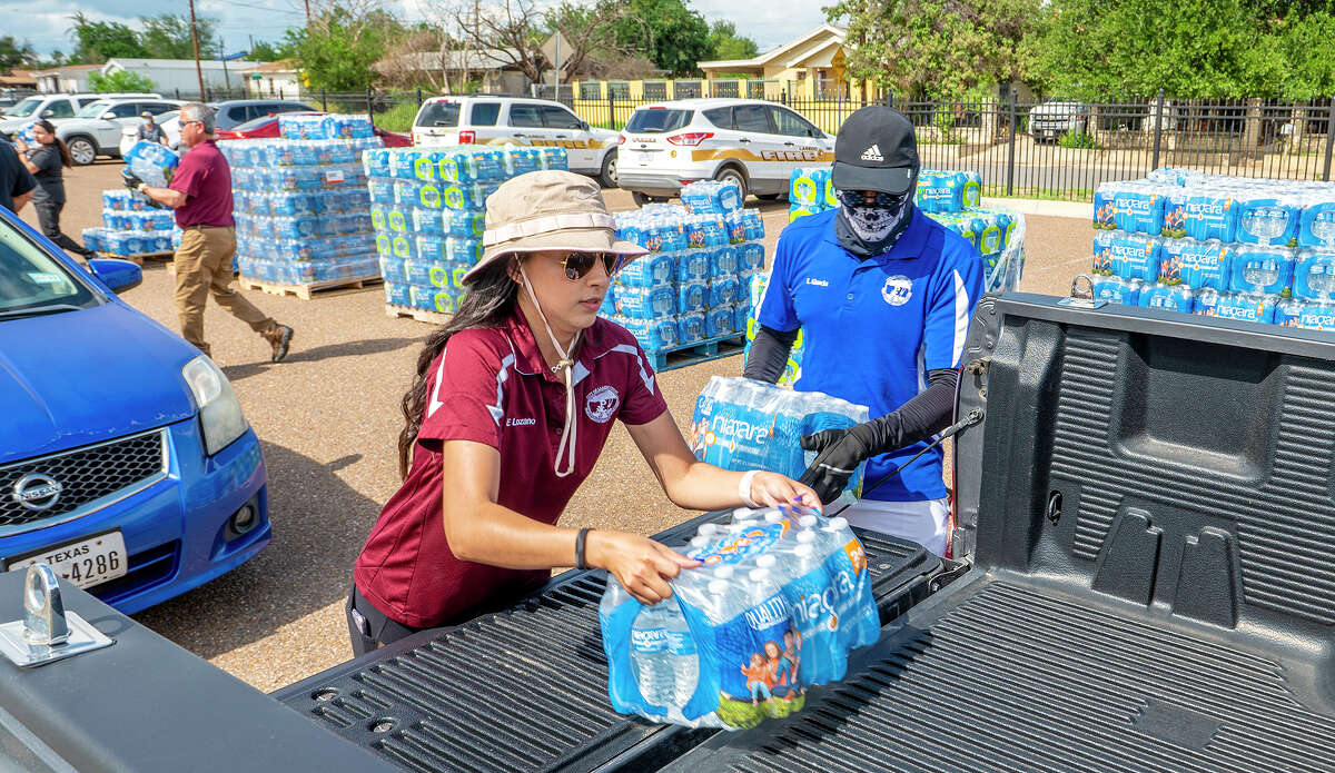 City of Laredo Parks and Recreation employees Eva Lozano and Leo Garcia help load cases of water onto vehicles during a water distribution at Slaughter Park, Friday, July 9, 2021, in response to the city wide boil water notice.