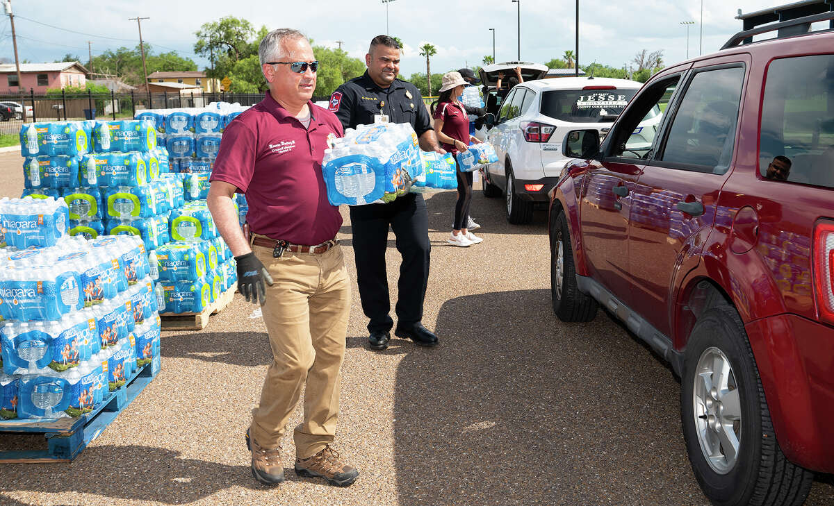City of Laredo councilmember Mercurio Martinez III and firefighter Ricardo Oliva Jr. help load cases of water onto vehicles during a water distribution at Slaughter Park, Friday, July 9, 2021, in response to the city wide boil water notice.