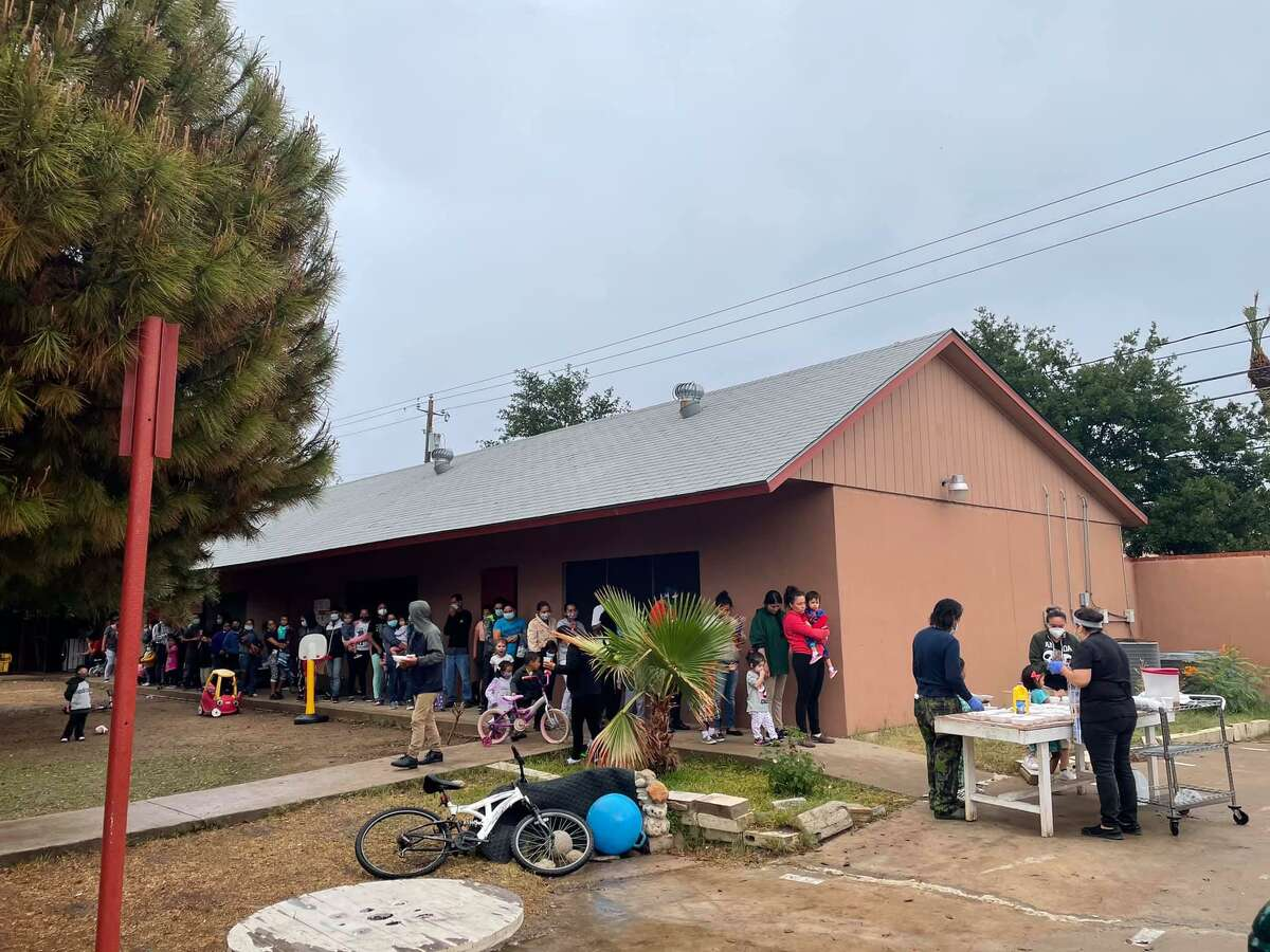 People wait in line for a meal distribution at the Holding Institute on May 1, 2021.