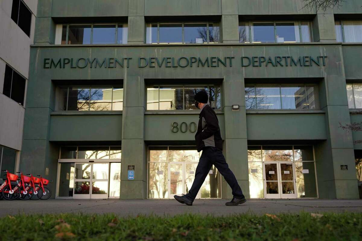 FILE - In this Dec. 18, 2020, file photo, a person passes the office of the California Employment Development Department in Sacramento, Calif. Americans who lost their job or some of their income in 2020 should pay attention to a new, one-time provision that ensures they don't lose access to valuable tax credits as well. (AP Photo/Rich Pedroncelli, File)