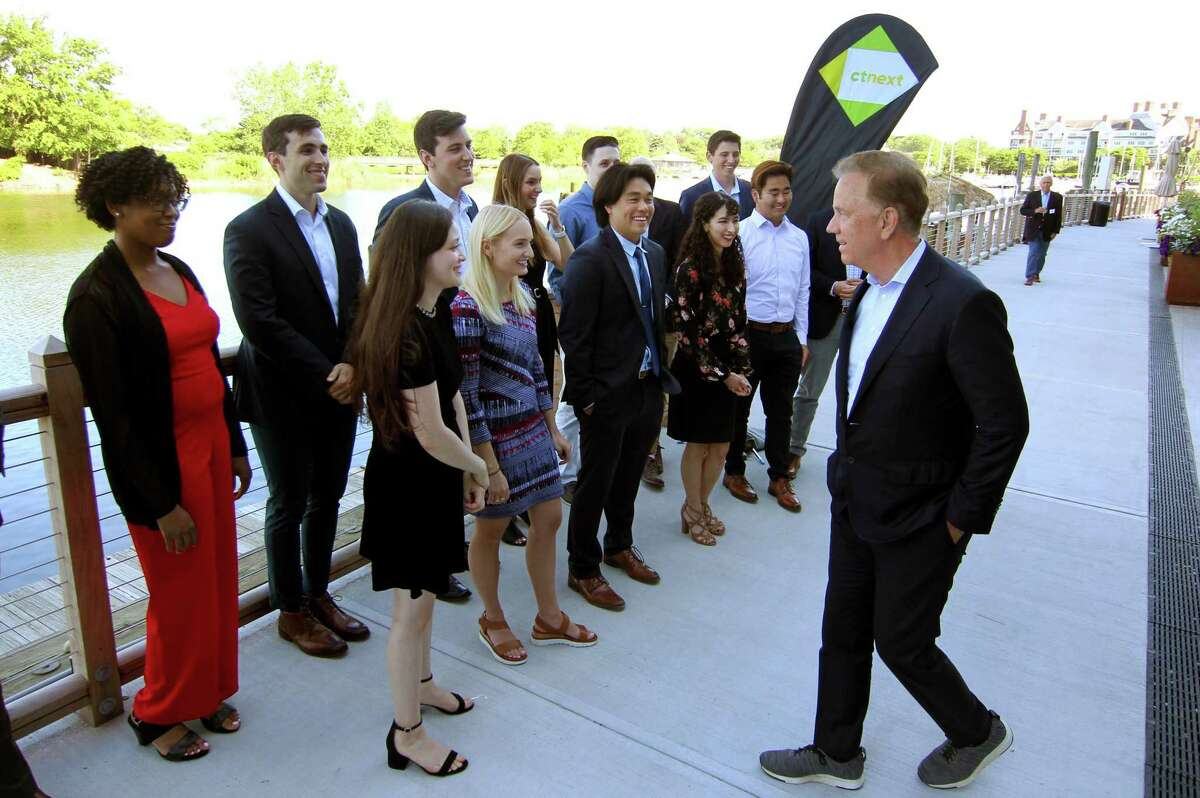 Gov. Ned Lamont greets graduates of the first class of the Governor's Innovation Fellowship during a reception at The Village in Stamford, Conn., on June 17, 2021.