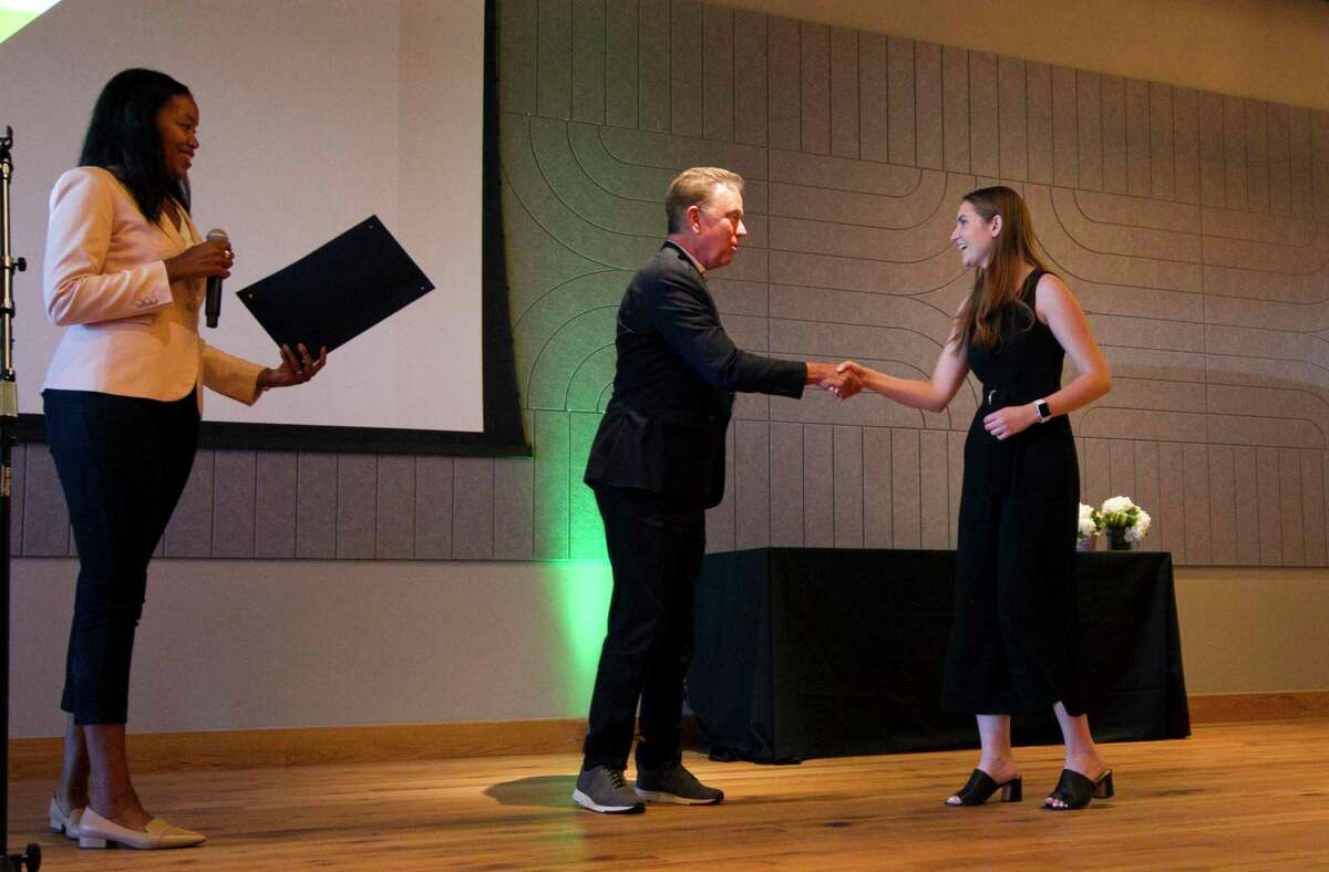 Gov. Ned Lamont shakes hands with Evan Duval, a University of Connecticut graduate who was a member of the first class of fellows in the Governor's Innovation Fellowship, during a reception at The Village in Stamford, Conn., on June 17, 2021.