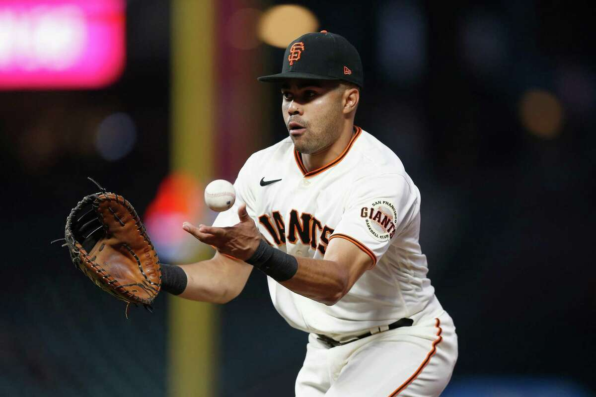 LaMonte Wade Jr. (31) of the San Francisco Giants tosses the ball to pitcher Johnny Cueto covering at first base to get the out against Jose Rondon of the St. Louis Cardinals on Tuesday.