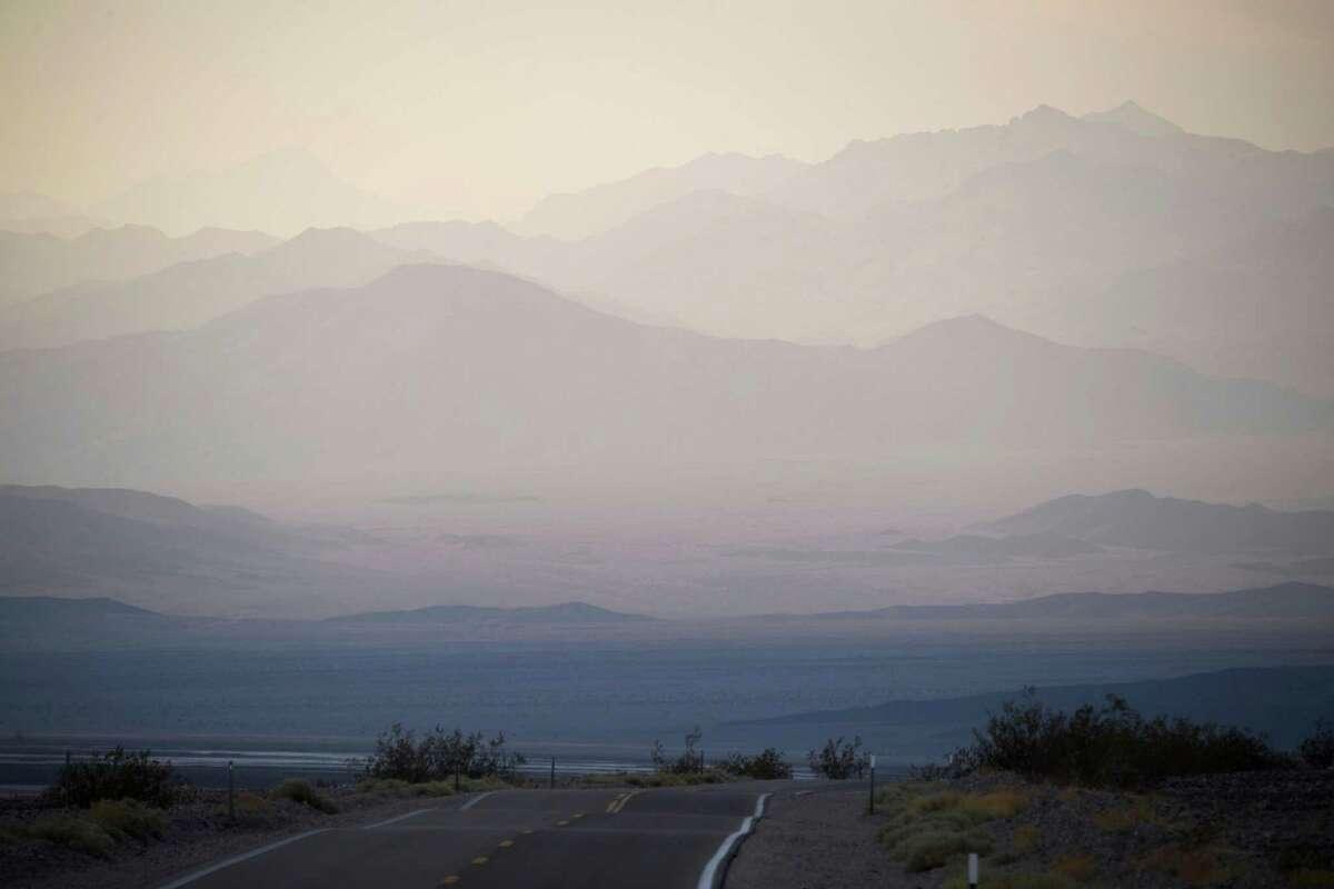 Layers of terrain peek through haze at sunset inside Death Valley National Park on June 17.