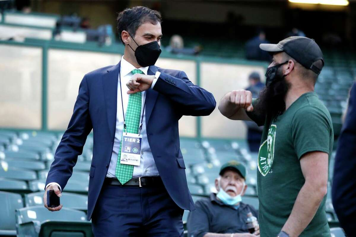 Oakland Athletics' president Dave Kaval elbow bumps a fan before A's play Houston Astros in season opener at Oakland Coliseum in Oakland, Calif., on Thursday, April 1, 2021.