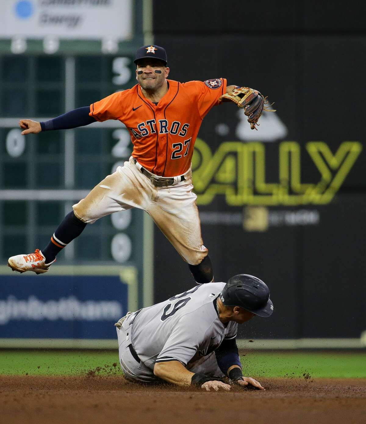 Houston Astros second baseman Jose Altuve (27) turns a double play against the New York Yankees during the seventh inning of an MLB game at Minute Maid Park on Friday, July 9, 2021, in Houston.