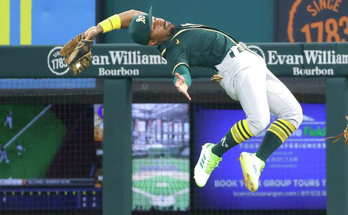 ARLINGTON, TX - JULY 9: Tony Kemp #5 of the Oakland Athletics makes a backward, leaping catch for an out off the bat of Isiah Kiner-Falefa #9 of the Texas Rangers during the first inning at Globe Life Field on July 9, 2021 in Arlington, Texas. (Photo by Ron Jenkins/Getty Images)