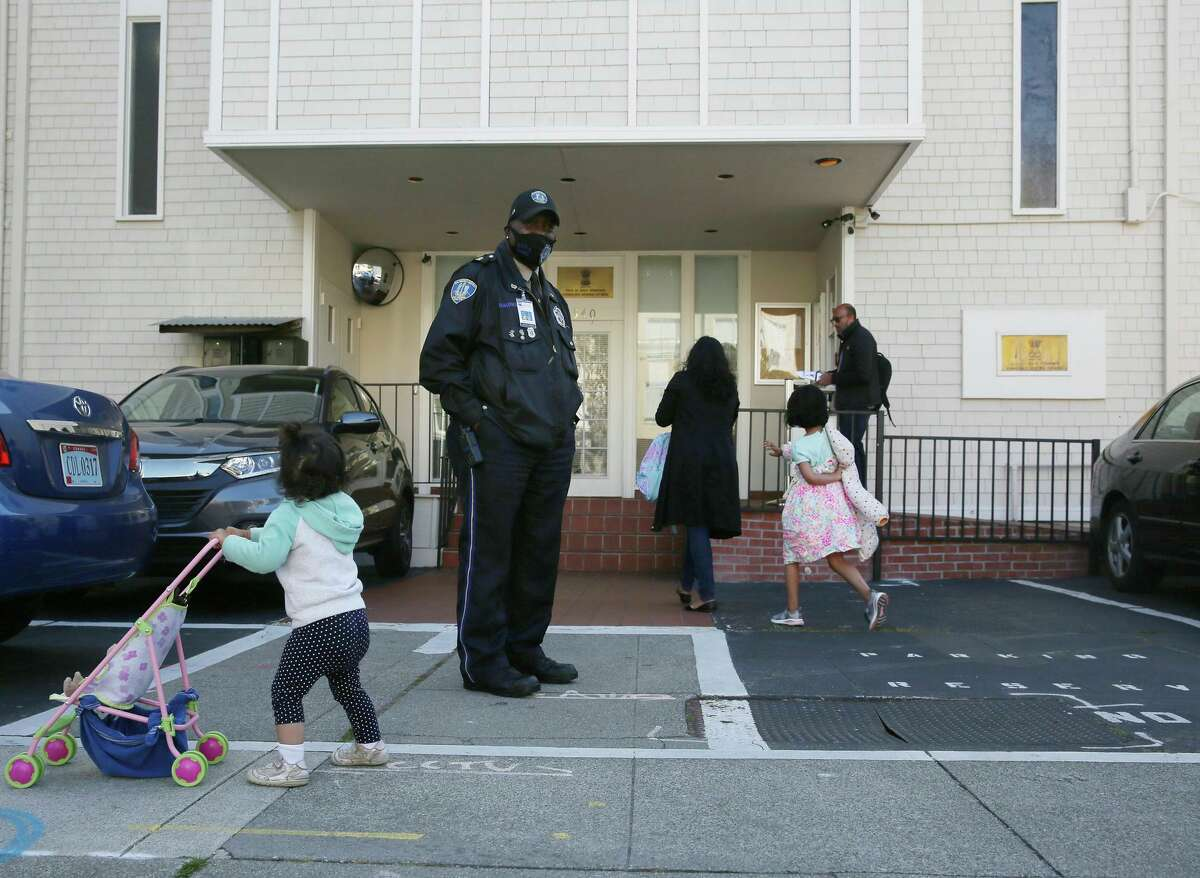 Security officer Billy Burke works at the Consulate General of India as Mithali Kamath, 1, pushes her stroller on Arguello Boulevard.
