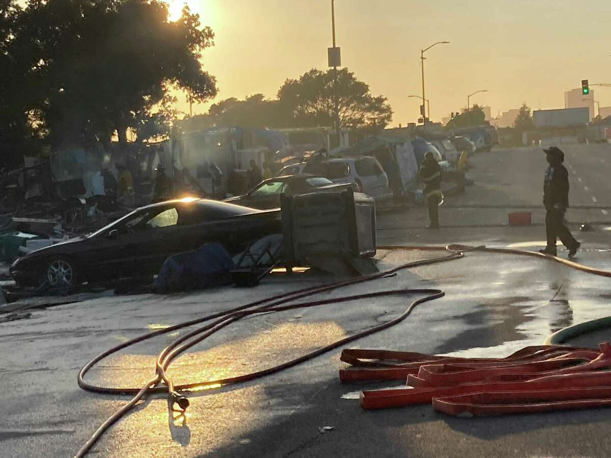 Ten people living at an encampment on East 12th Street in Oakland were displaced Friday after a large fire burned through the area, fire officials said.