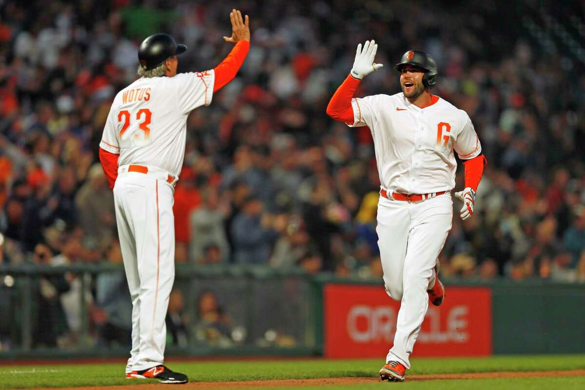 San Francisco Giants first baseman Darin Ruf (33) high fives Giants third base coach Ron Wotus (23) as Ruf jogs to home plate after hitting a homer in the fifth inning during an MLB game against the Washington Nationals at Oracle Park, Friday, July 9, 2021, in San Francisco, Calif.