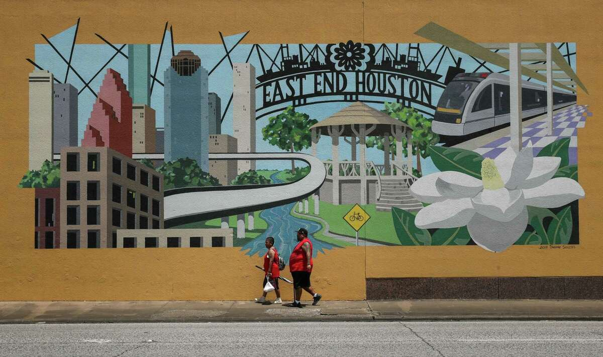 A couple walks by a mural Tuesday, July 6, 2021, near the intersection of South Wayside Drive and Capitol Street in Houston.