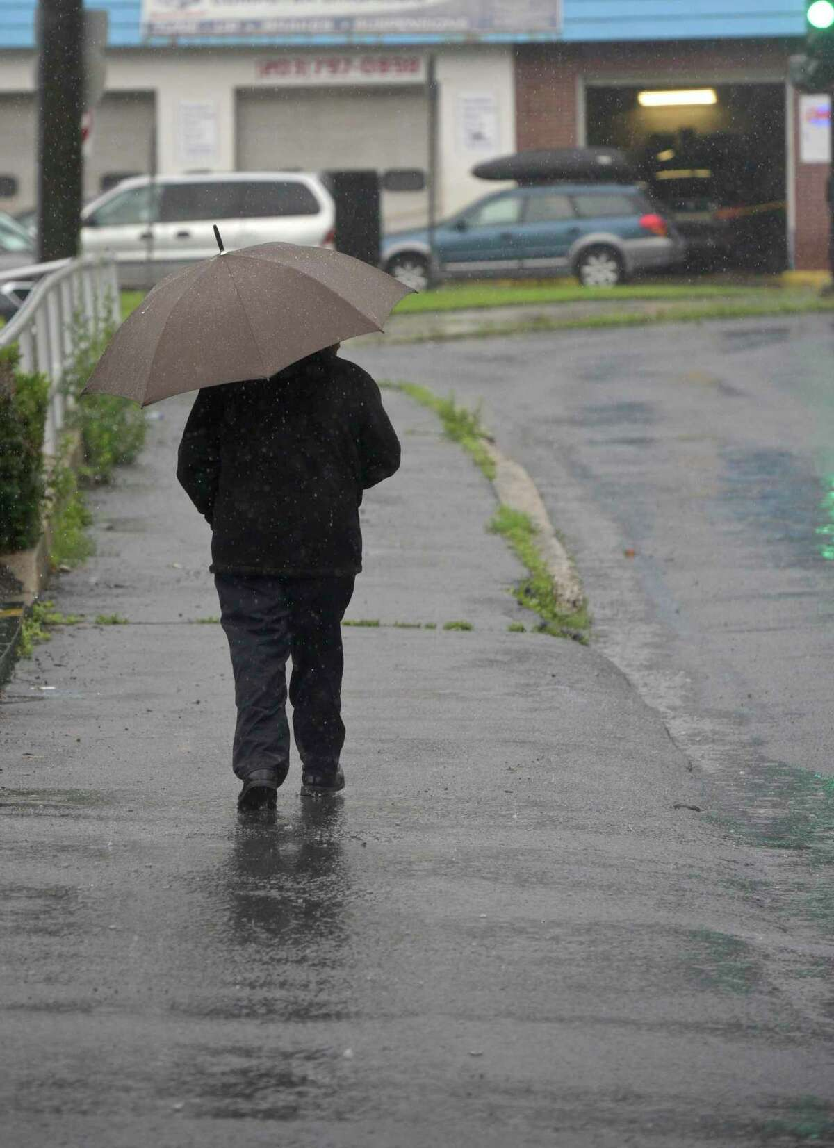 A pedestrian walks along West Street during tropical storm Elsa, in Danbury, Ct, on Friday, July 9, 2021.