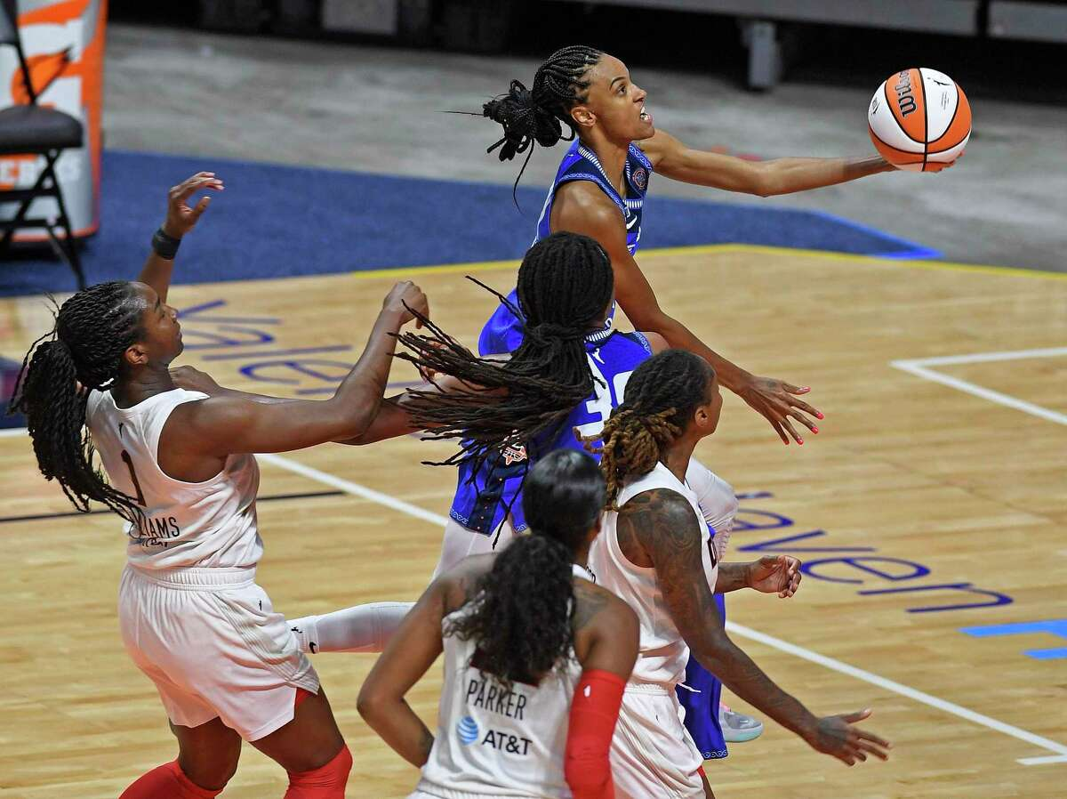 Connecticut Sun forward DeWanna Bonner glides to the basket ahead of Atlanta Dream defender Elizabeth Williams, left, and in front of teammate Jonquel Jones and Dream defenders Cheyenne Parker and Crystal Bradford during a WNBA basketball game Friday, July 9, 2021, in Uncasville, Conn. (Sean D. Elliot/The Day via AP)