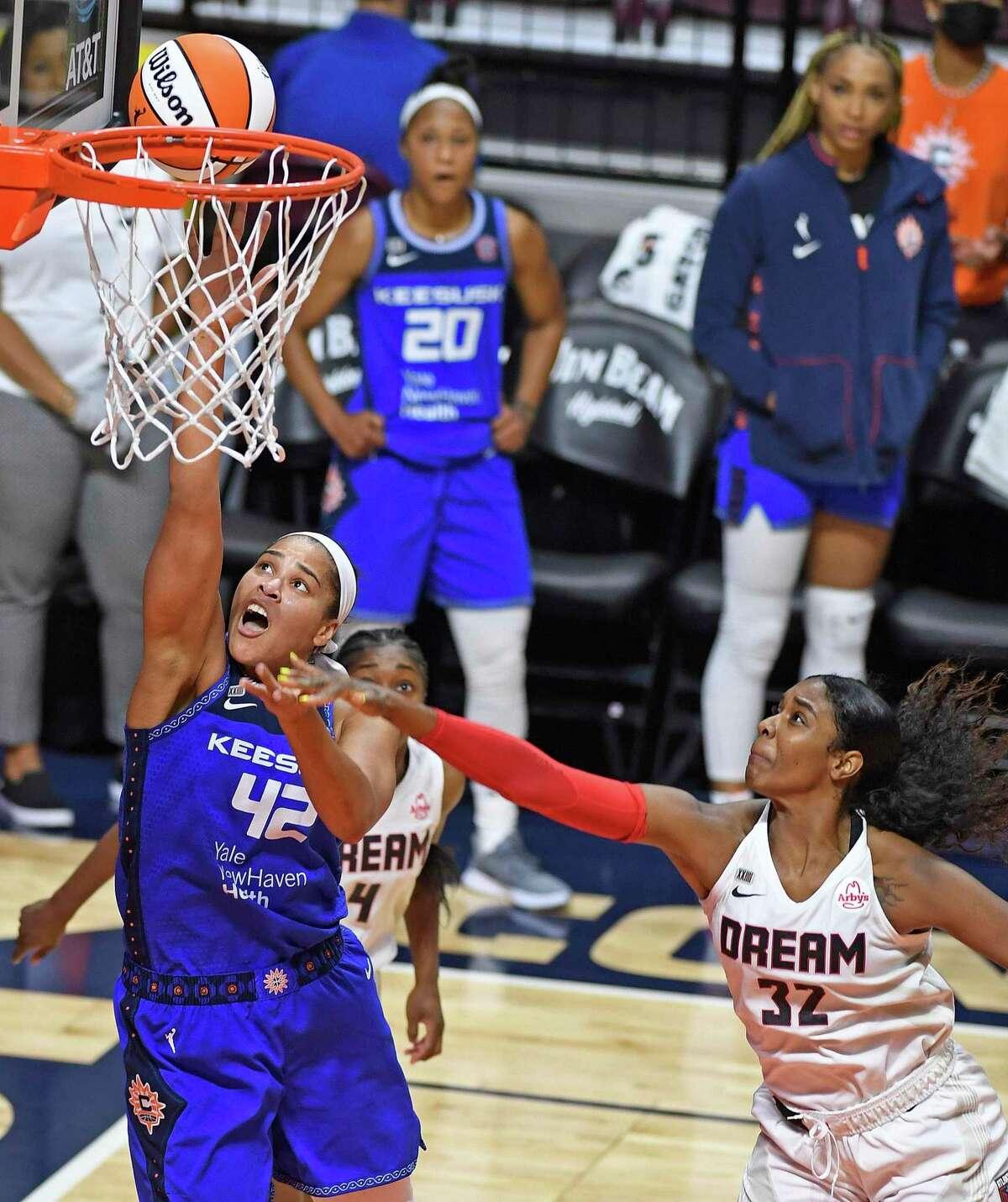 Connecticut Sun center Brionna Jones (42) scores around the defense of Atlanta Dream forward Cheyenne Parker (32) during a WNBA basketball game Friday, July 9, 2021, in Uncasville, Conn. (Sean D. Elliot/The Day via AP)