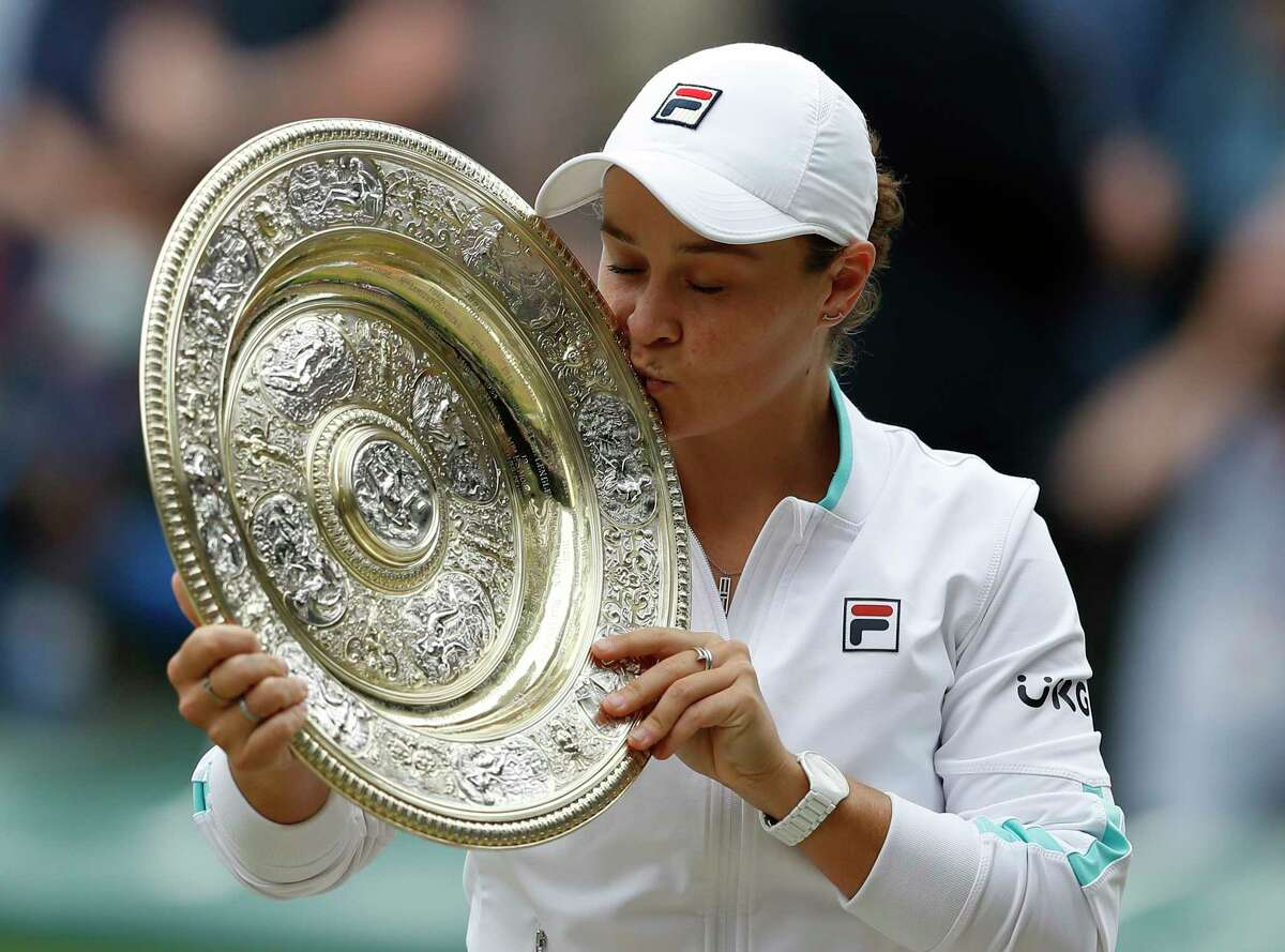 Australia's Ashleigh Barty poses with the trophy for the media after winning the women's singles final after defeating the Czech Republic's Karolina Pliskova on day twelve of the Wimbledon Tennis Championships in London, Saturday, July 10, 2021. (Pete Nichols/Pool Via AP)