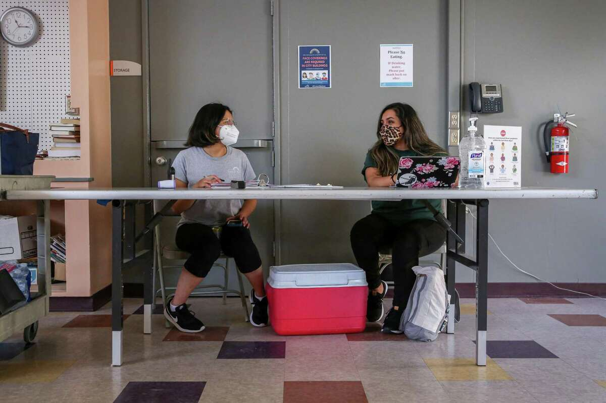 From left, recreation leaders Mariah Tapia and Nicole Rodriguez Calderon chat while at a screening station in a cooling center at Camden Community Center in San Jose, Calif. on Wednesday, June 16, 2021. The cooling station was open again on Saturday, July 10, 2021, amid another scorching heat wave.