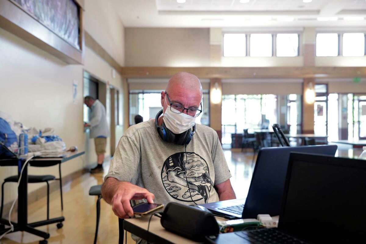 Shawn Busick checks his email and charges his electronic devices while trying to keep out of the intense heat at the cooling center set up at the Concord Senior Citizens Center in Concord, Calif., on Monday, Sept. 7, 2020. The library was one of more than 30 locations in Contra Costa County to reopen as a cooling center on Saturday, July 10, 2021, as triple-digit temperatures scorched the region.