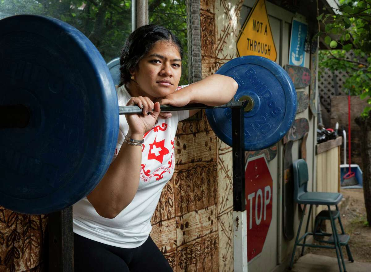 A portrait of Kuinini Manumua with weightlifting equipment in the backyard of her aunt, Wednesday, July 7, 2021, in San Bruno, Calif. Manumua, who also goes by the nickname Nini, will represent Tonga in women's weightlifting in the Tokyo 2020 Summer Olympics. She trained in the backyard of her aunt's home, as gyms closed during the coronavirus pandemic.