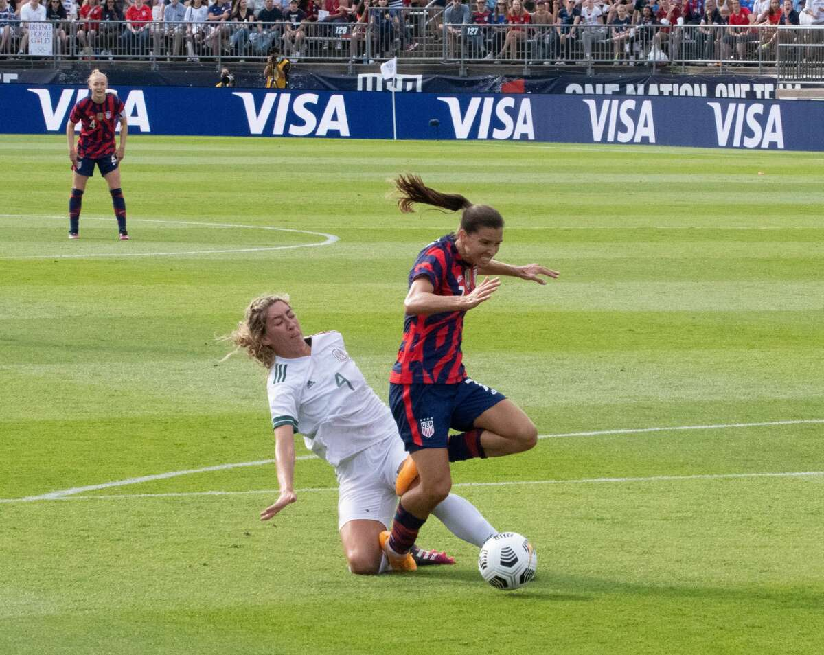 Tobin Heath of the US Women's Soccer National Team gets tackled by Mexico's Jocelyn Orejel during a Send-Off Series match against Mexico at Pratt & Whitney Stadium in East Hartford, Conn. on Monday, July 5, 2021. The U.S. won 4-0 over Mexico. (Joyce Bassett / Special to the Times Union)