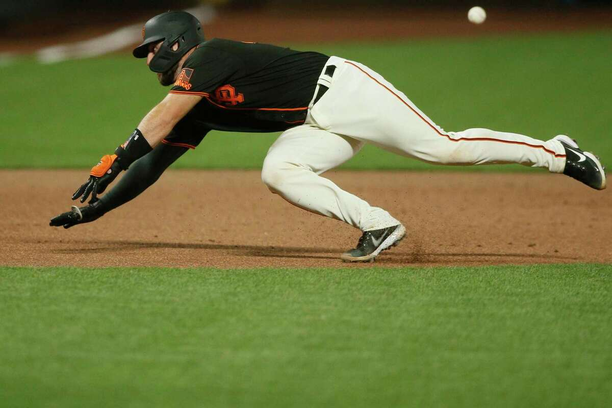 After hitting a triple on a line drive to center field that scores the Giant's Brandon Belt, San Francisco Giants Joey Bart (21) slides safe to third base in the sixth inning during an MLB game against the Arizona Diamondbacks at Oracle Park, Saturday, Sept. 5, 2020, in San Francisco, Calif.