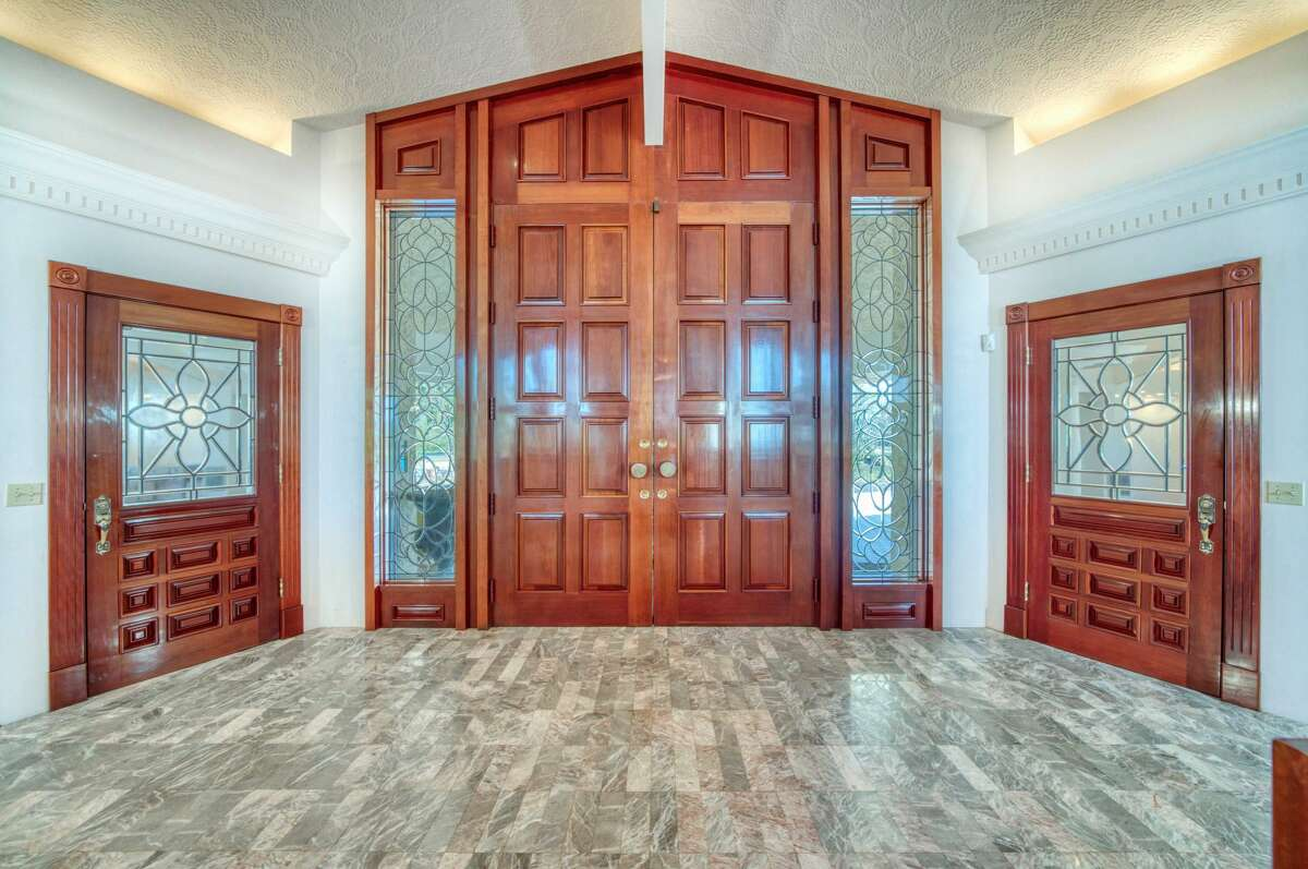 The entry door is of carved wood and the floor is marble.