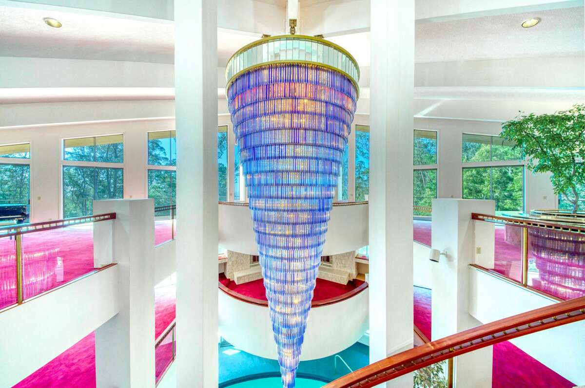 The chandelier dangles between the home's levels, its blue cast reflected in the pool, glimpsed below.