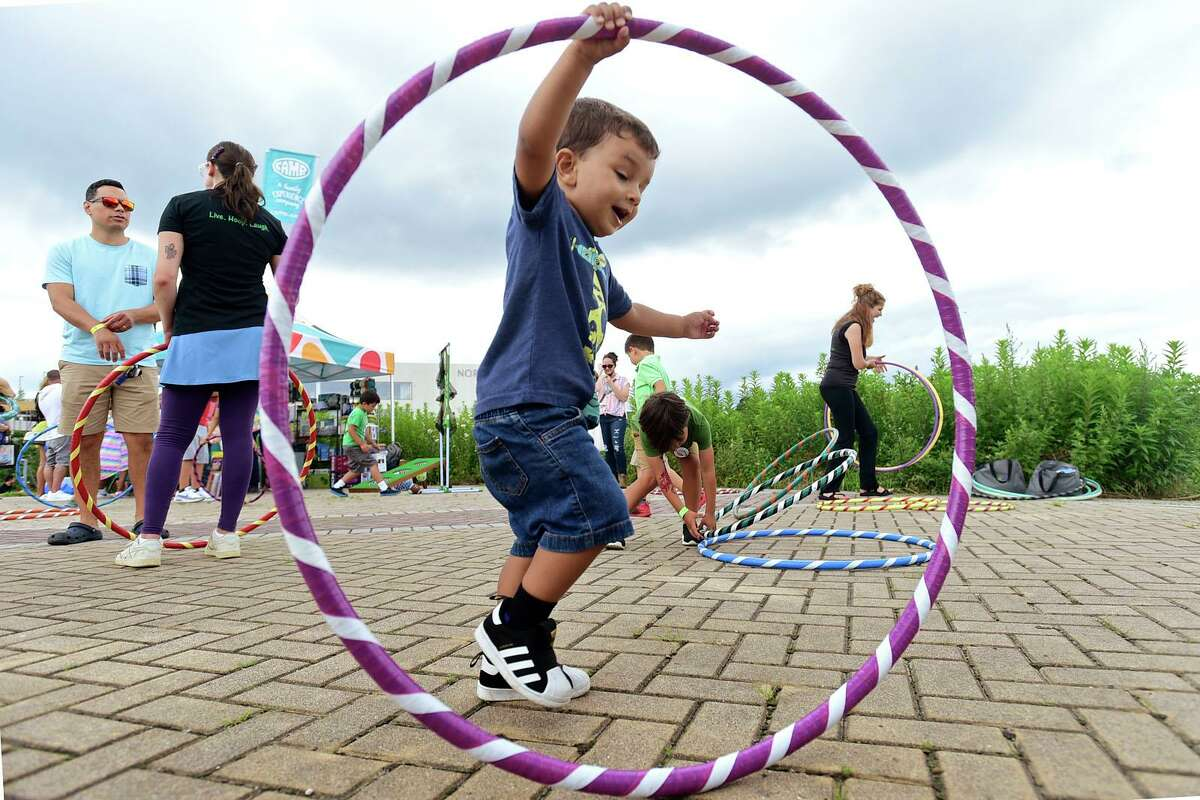 Giacchino Mrmus, 3, plays with a hoola hoop at the Child of the World Stage during the annual Nice Festival Saturday, July 10, 2021, at Oyster Shell Park in Norwalk, Conn.