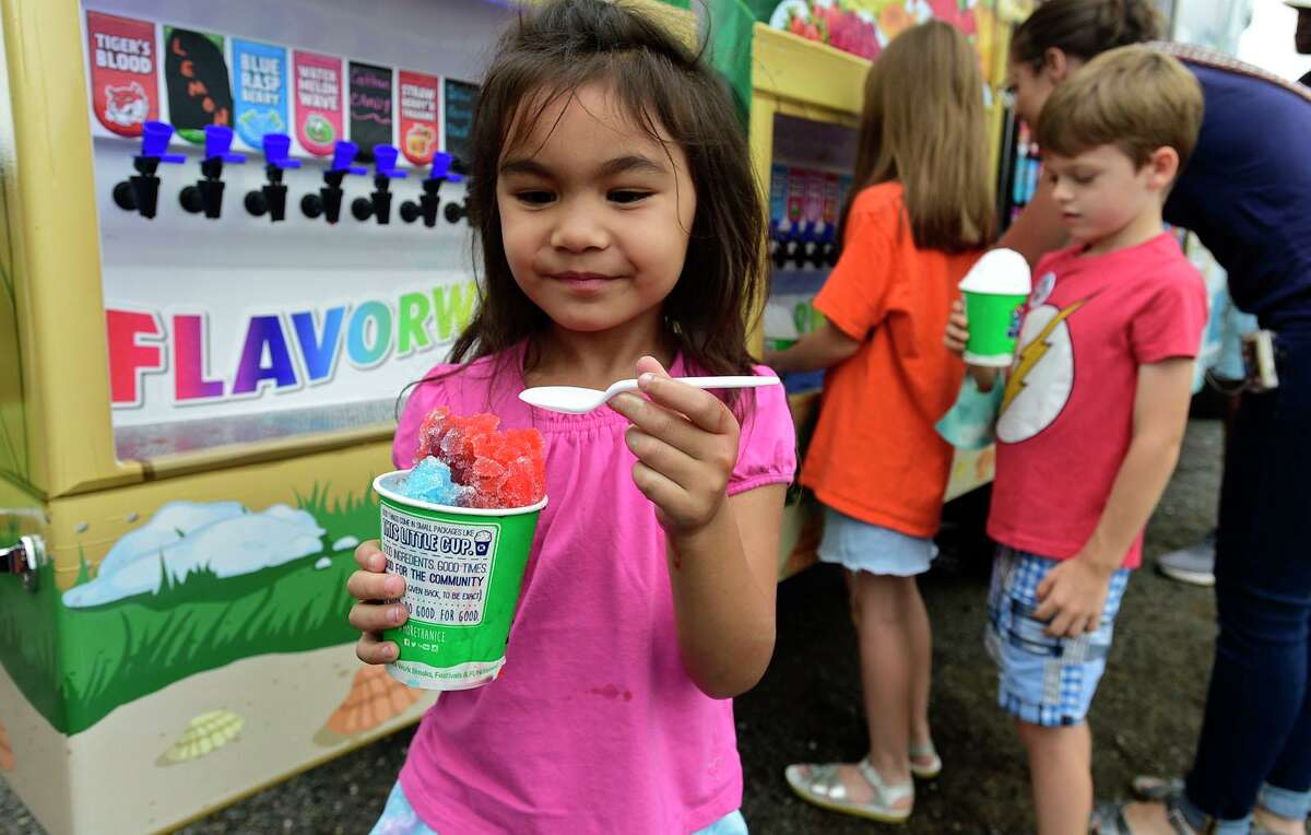 Priya Greenspan, 5, eats a snow cone during the annual Nice Festival Saturday, July 10, 2021, at Oyster Shell Park in Norwalk, Conn.