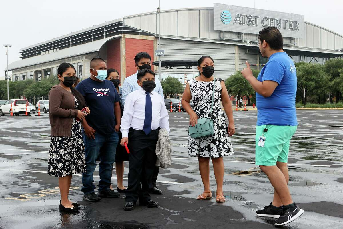 Aurelio Alcocer, from right, with Metro Health, greets Elsi Cabrera; Nathan Mendez, 9; Jonathan Mendez, 17; Jessica Mendez, 13; Esdras Mendez; and Jennifer Mendez, 14, as they arrive at the AT&T Center on Saturday for a vaccination clinic.