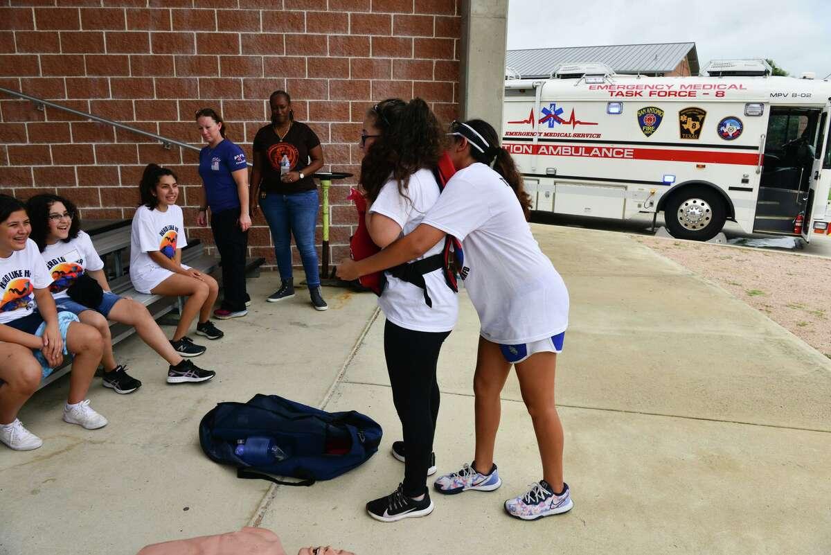 Gilliann Cantu and Savanna Rocha go through a drill Saturday at the San Antonio Fire Department Training Academy camp.
