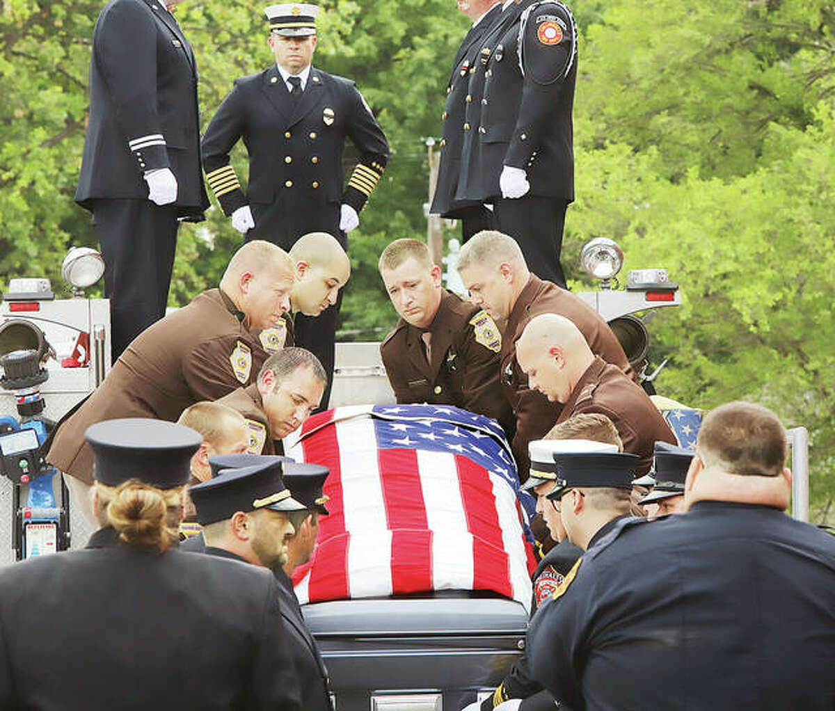 """An honor guard from the Madison County Sheriff's Department and local firefighters lift the flag-drapped casket of South Roxana Fire Chief William """"Todd"""" Werner onto the back of South Roxana Fire Engine 3110 Saturday following his funeral at the Roxana Church of the Nazarene Theater."""