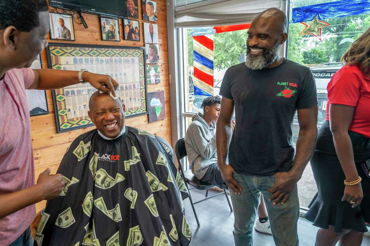 Mayor Sylvester Turner laughs as he receives a haircut and talks to Gabriel Ismael, right, during a vaccine awareness event Saturday at Goode Looks Barber Shop on Scott Street.