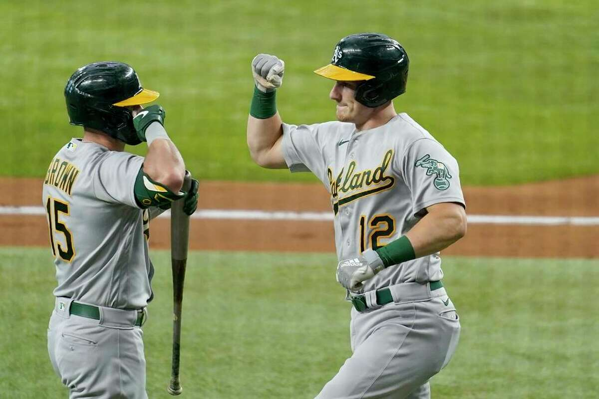 Oakland Athletics' Seth Brown (15) and Sean Murphy (12) celebrate a solo home run hit by Murphy in the second inning of a baseball game against the Texas Rangers in Arlington, Texas, Saturday, July 10, 2021. (AP Photo/Tony Gutierrez)
