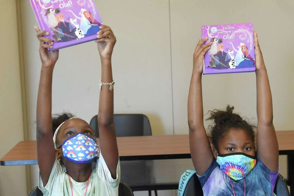 Neveah Gates (left) and Beloved Garrett hold up their books as they get ready to read during Augusta's Angels' summer reading and feeding program for children at the Gloria Ramirez Resource Center Tuesday, July 6. Photo made Tuesday, July 6, 2021 Kim Brent/The Enterprise