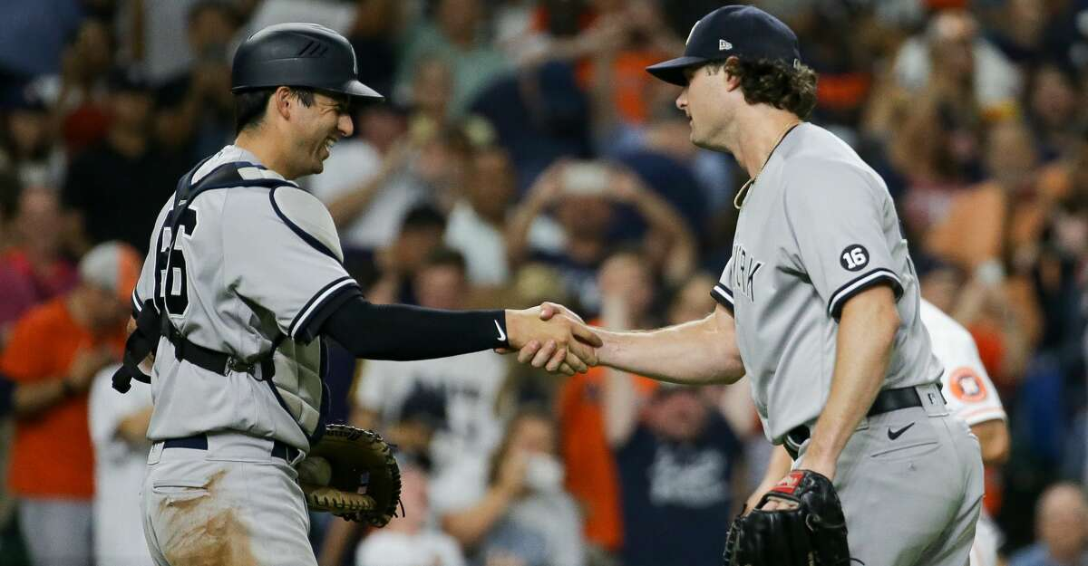 New York Yankees starting pitcher Gerrit Cole (45) celebrates with catcher Kyle Higashioka (66) after throwing a complete game shutout against the Houston Astros at Minute Maid Park on Saturday, July 10, 2021, in Houston.