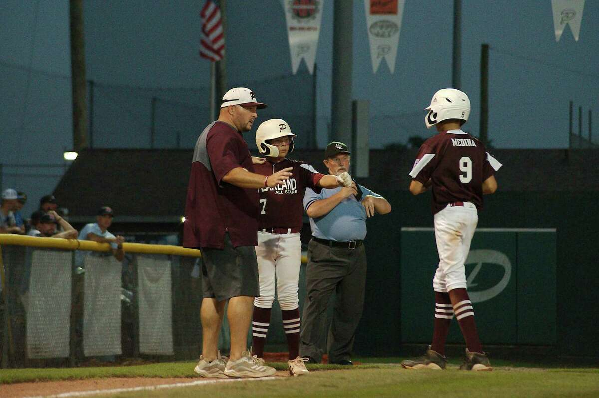 Pearland East All Stars' coach Jeff Sills chats with Isaac Huerta and Oscar Medina during a time out against Post Oak Little League in the section 3 championship game Saturday in Pearland.