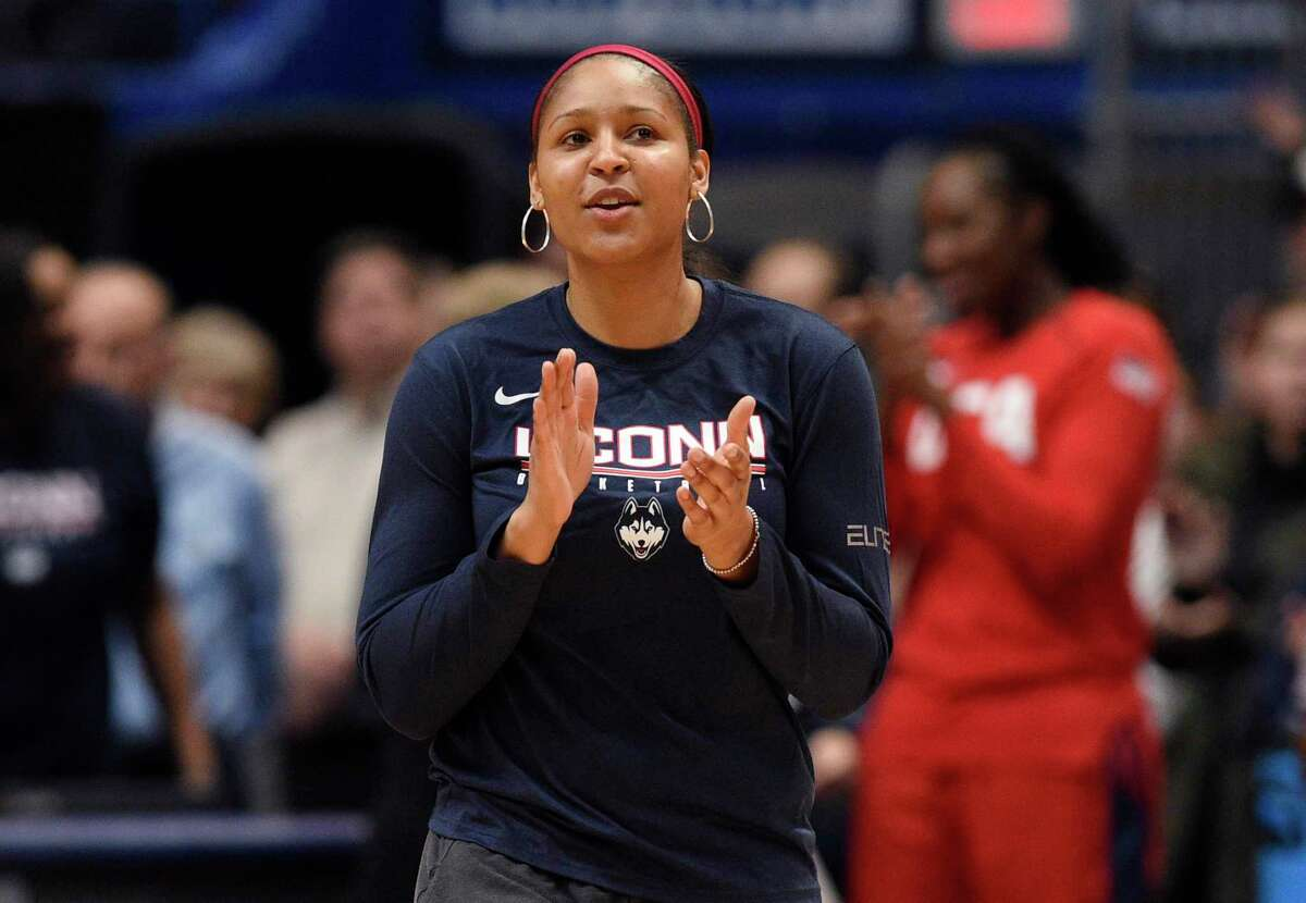 """FILE - In this Jan. 27, 2020, file photo, former Connecticut and Minnesota Lynx player Maya Moore applauds in Hartford, Conn. Moore left the WNBA in 2019 to help her now husband Jonathan Irons get his conviction overturned and win his release from prison. Moore, 32, remains non-committal to returning to the WNBA. A documentary of their story - """"Breakaway"""" - that was produced by Robin Roberts will air next week on ESPN. (AP Photo/Jessica Hill, File)"""