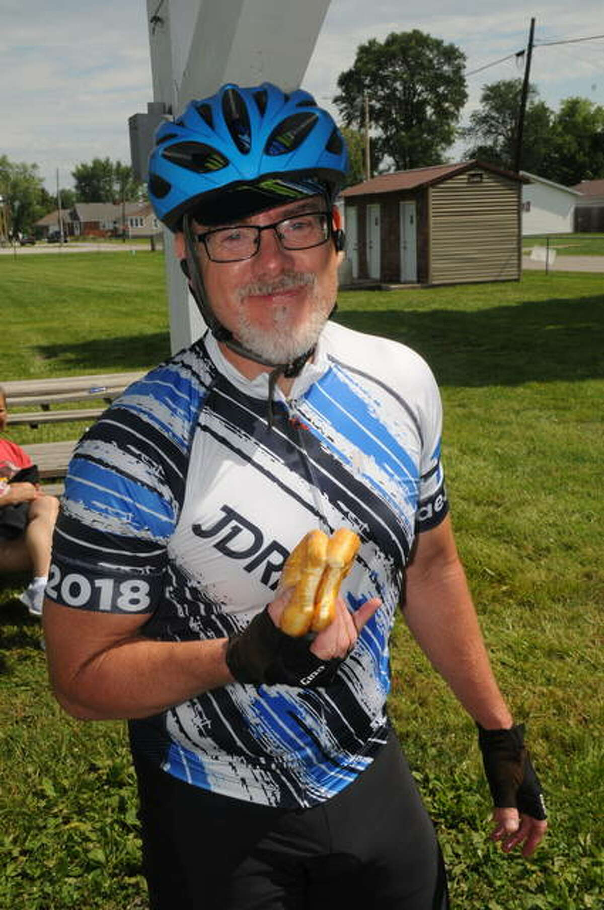 """Kevin Lilly of Naperville, Illinois munches donuts during the Eagarville stop on Saturday's Tour de Donut. The 32nd annual event in Staunton featured hundreds of bicyclists competing in a full 34-mile or a """"donut hole"""" 12-mile course."""