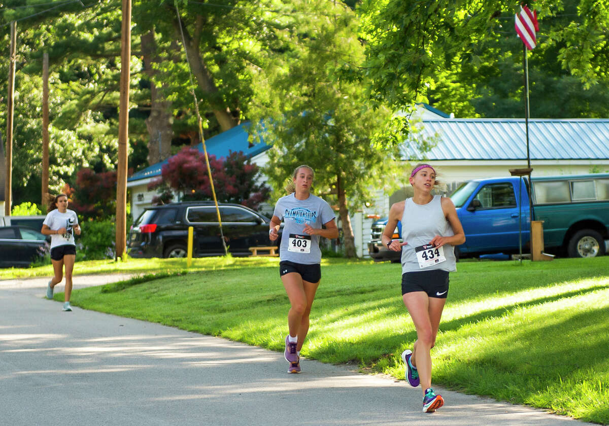From left, Elizabeth Smith, Lauren Brawt and Ann Wittbrodt participate in the Coach Cole Memorial 5K run/walk Saturday, July 10, 2021 in downtown Sanford. (Adam Ferman/for the Daily News)
