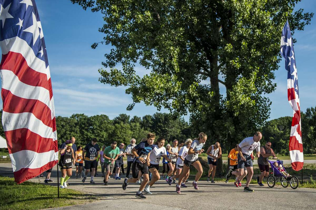 Runners and walkers take off from the starting line during the Coach Cole Memorial 5K run/walk Saturday, July 10, 2021 in downtown Sanford. (Adam Ferman/for the Daily News)