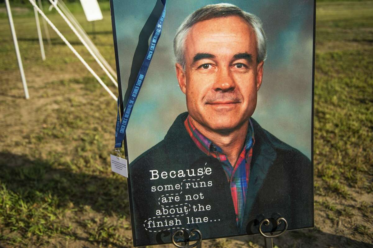 A photo of Bob Cole is displayed while runners and walkers participate in the Coach Cole Memorial 5K run/walk Saturday, July 10, 2021 in downtown Sanford. (Adam Ferman/for the Daily News)