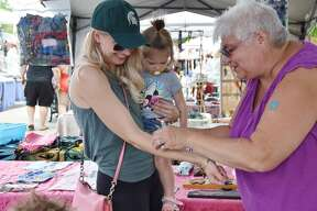 (From left) Loren Eisenlohr holds Jazz Eisenlohr while receiving a Wonder Woman glitter tattoo by Char Quade, of Char's Crafts Saturday.