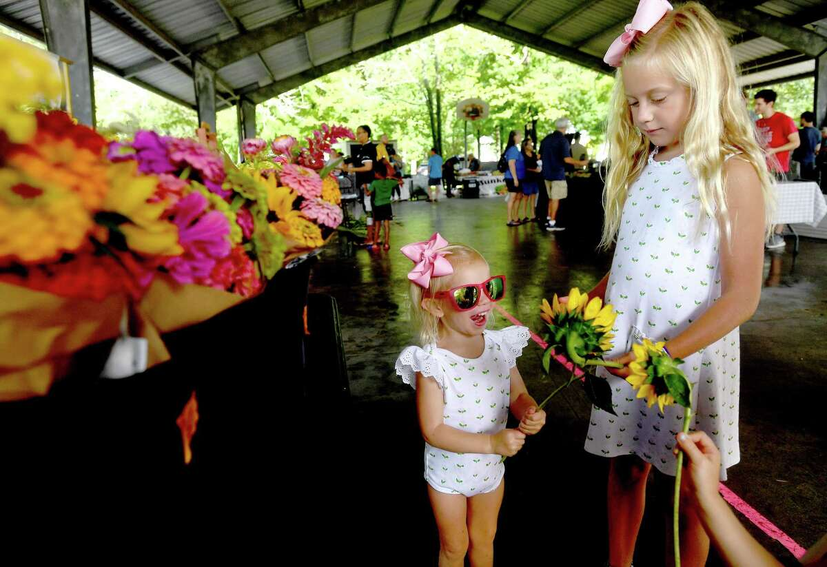 Mary Crawford Davis (left) and sister Palmer Kate admire the sunflowers given to them by Brent Heironimus as they and family select a bouquet of flowers from the Donna's Farm stand at the Beaumont Farmer's Market Saturday. Photo made Saturday, July 10, 2021 Kim Brent/The Enterprise