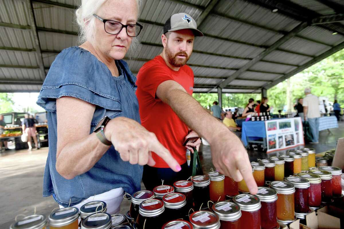 Jennifer and son Travis Freeman select jams from Debbie Givens' stand at the Beaumont Farmer's Market Saturday. Photo made Saturday, July 10, 2021 Kim Brent/The Enterprise